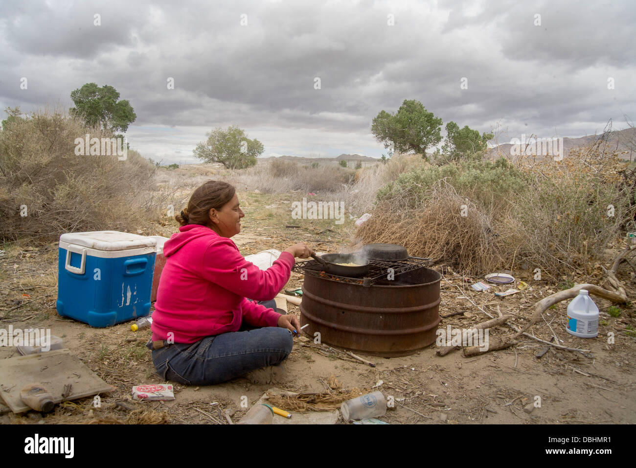 A homeless woman cooks corn on a primitive outdoor grill a primitive outdoor encampment in the desert town of Victorville, - Stock Image