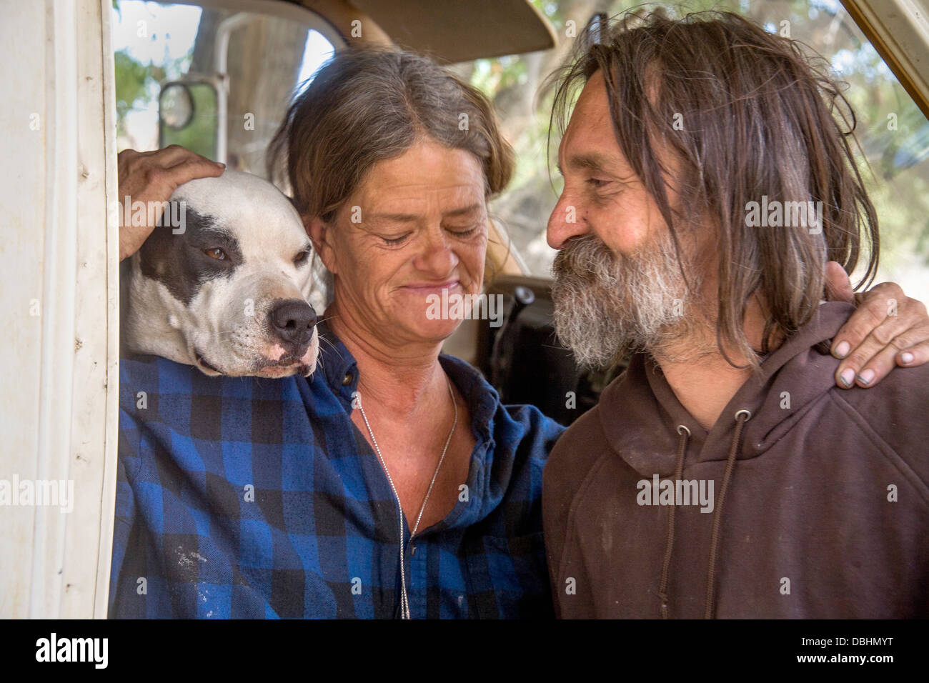 An affectionate indigent couple and their dog live in a truck camper among homeless residents of a primitive outdoor - Stock Image
