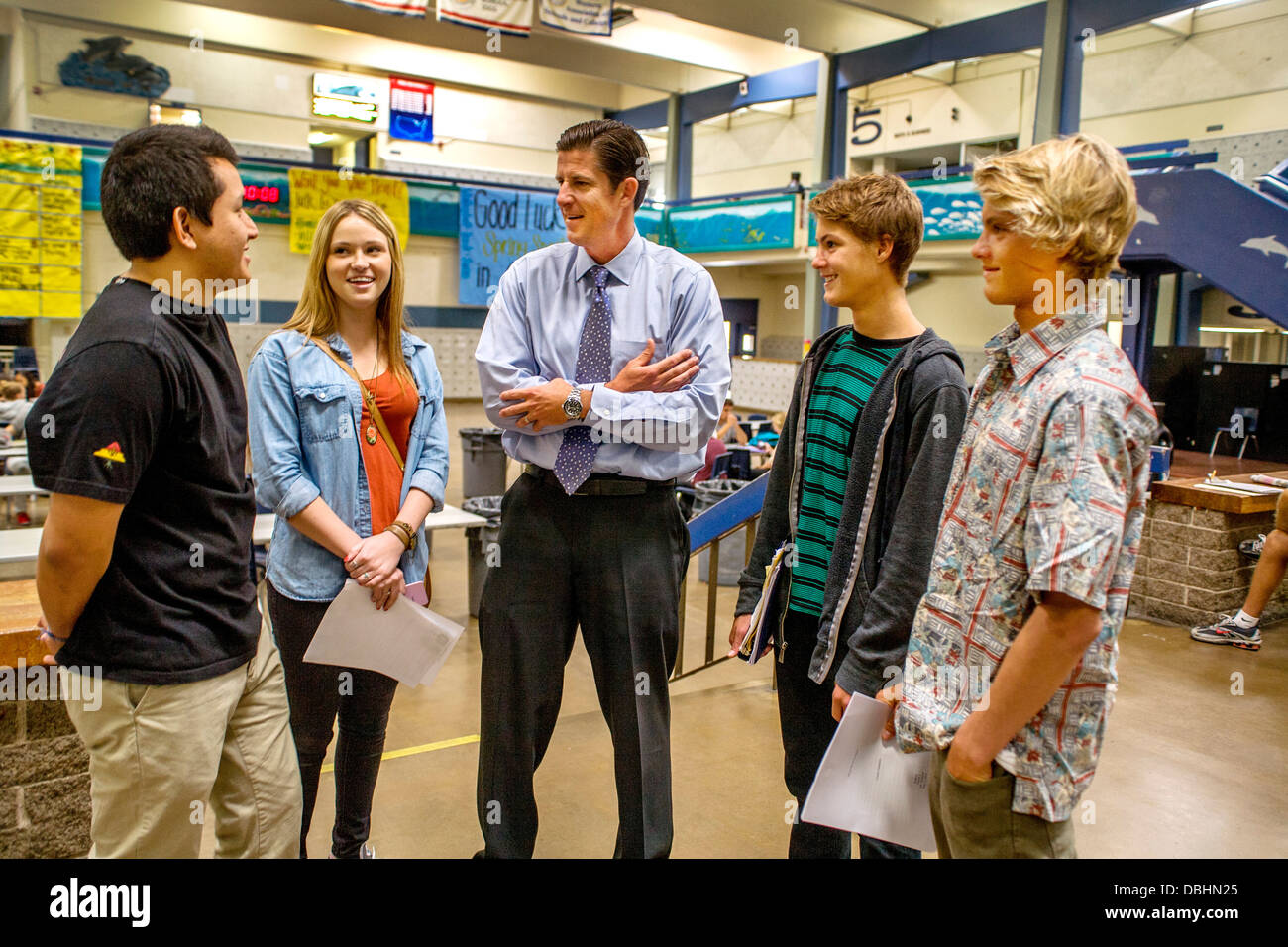 A high school principal talks with four of his students in the school building atrium in Dana Point - Stock Image