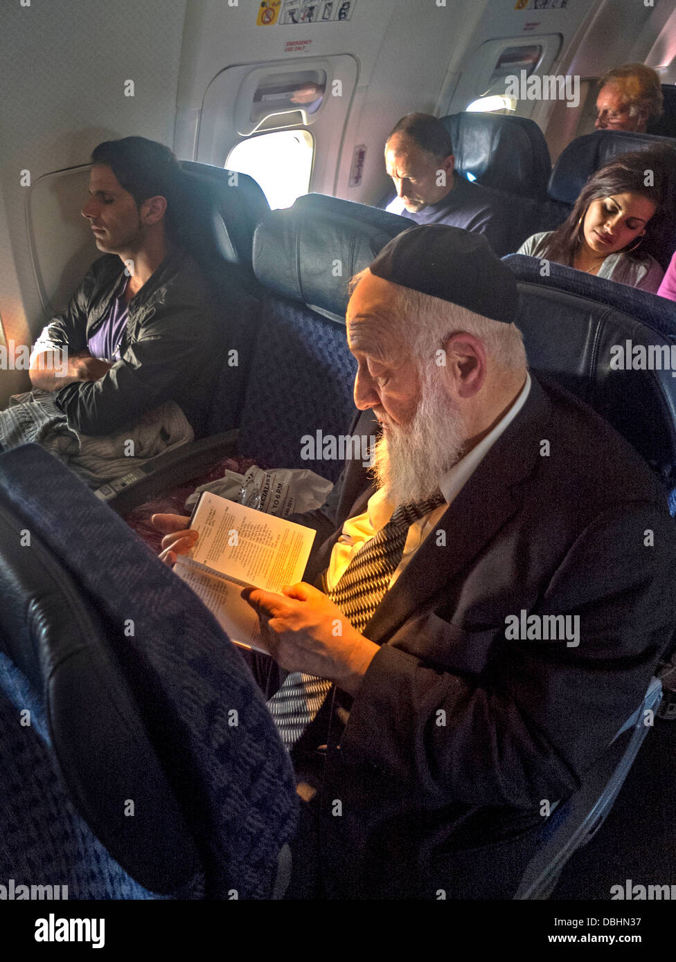 Wearing a yarmulke skull cap, an bearded Orthodox Jew reads from a book in Hebrew on an airliner - Stock Image
