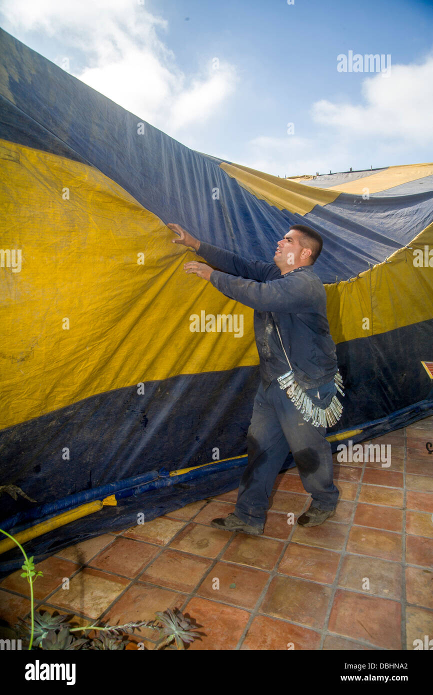 Hispanic workmen in Laguna Niguel, CA, cover a home with a gasproof tent prior to fumigation - Stock Image