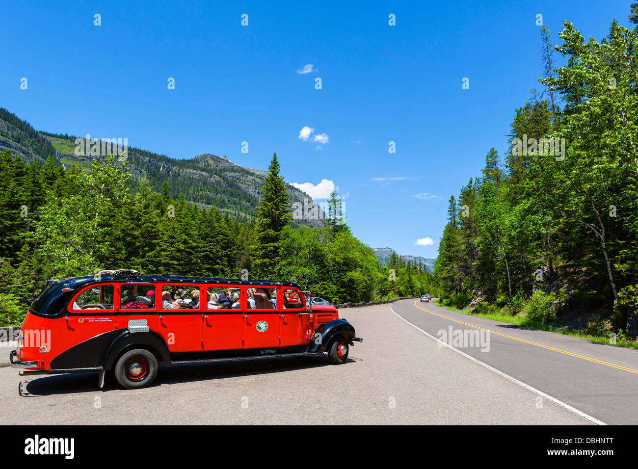 Red Bus Tour in the parking area of McDonald Falls, Going to the Sun Road, Glacier National Park, Montana, USA - Stock Image