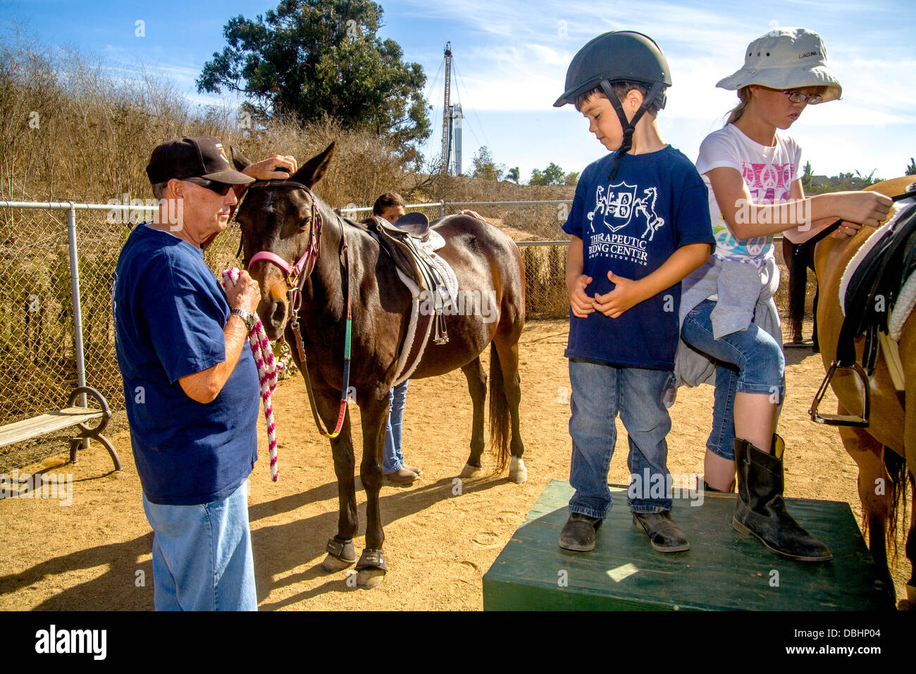 A boy affilicted with Von Wellebrand Disease and high-function autism prepares to ride a horse as part of therapeutic - Stock Image