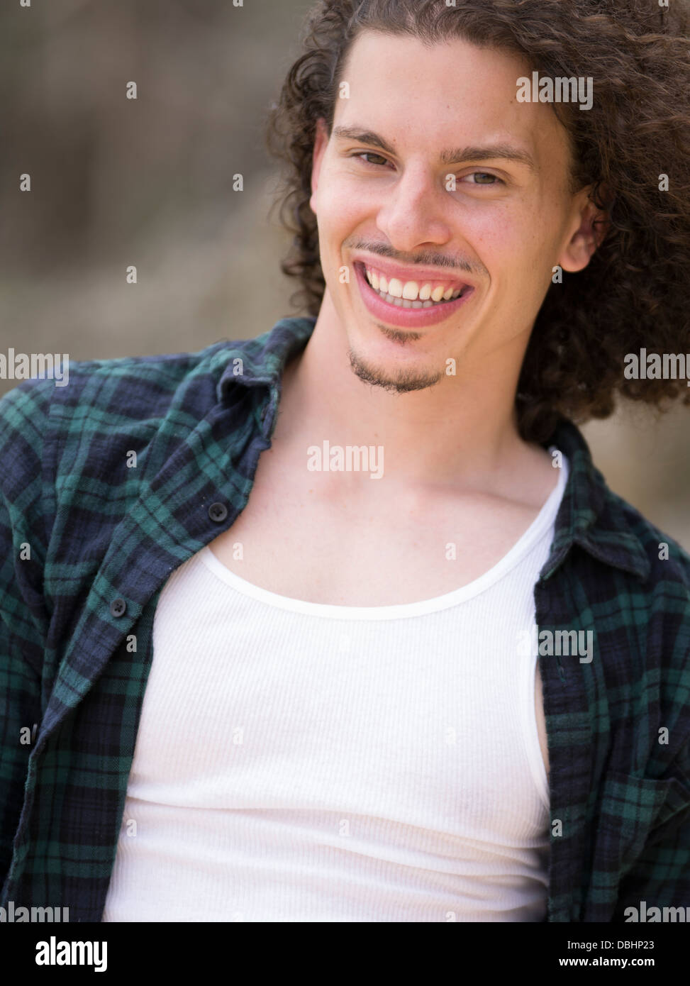 Egyptian American Man with long wavy hair beard and mustache smiling wearing check shirt and white t-shirt - Stock Image