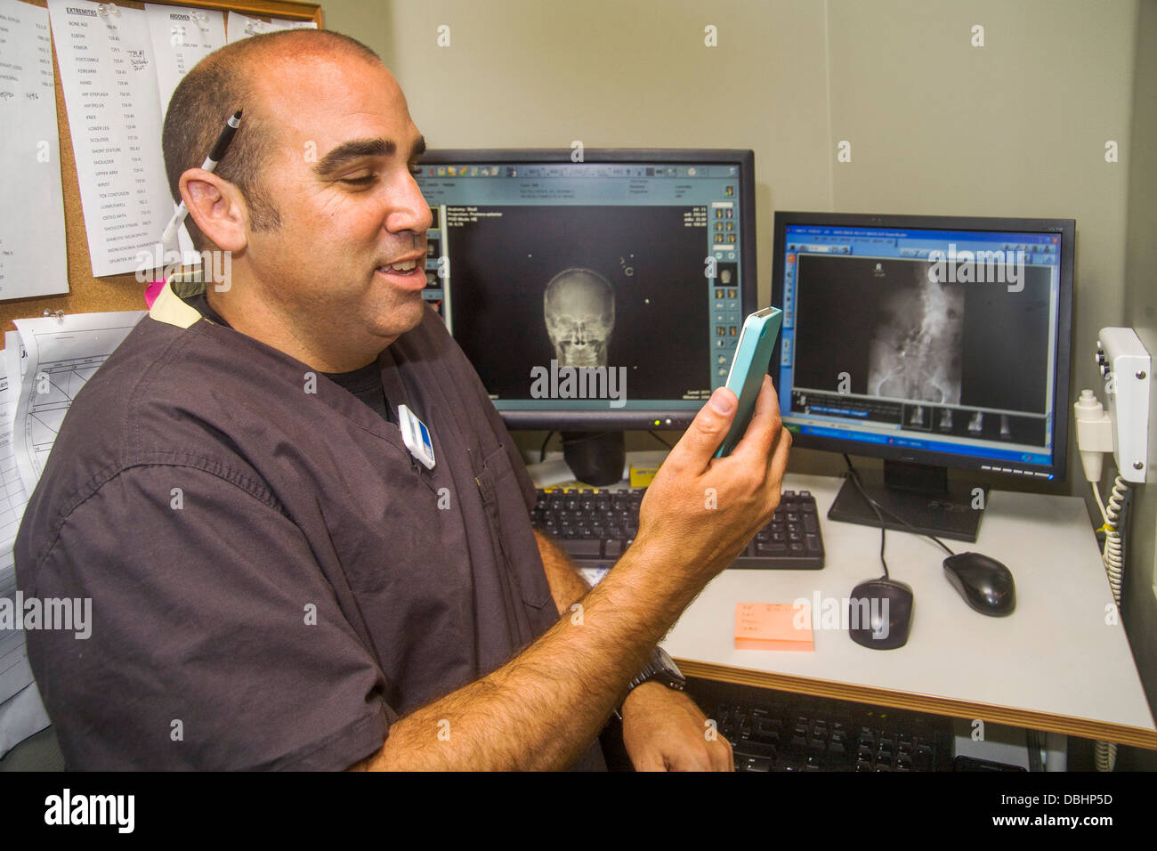 A radiologist dictates into an iPhone at a digital work station in a Laguna Hills, CA, clinic. Note monitors in - Stock Image