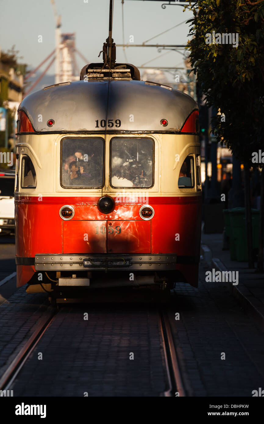 Red and cream electric trolley car gleams in sunlight as it hurries along San Francisco street - Stock Image