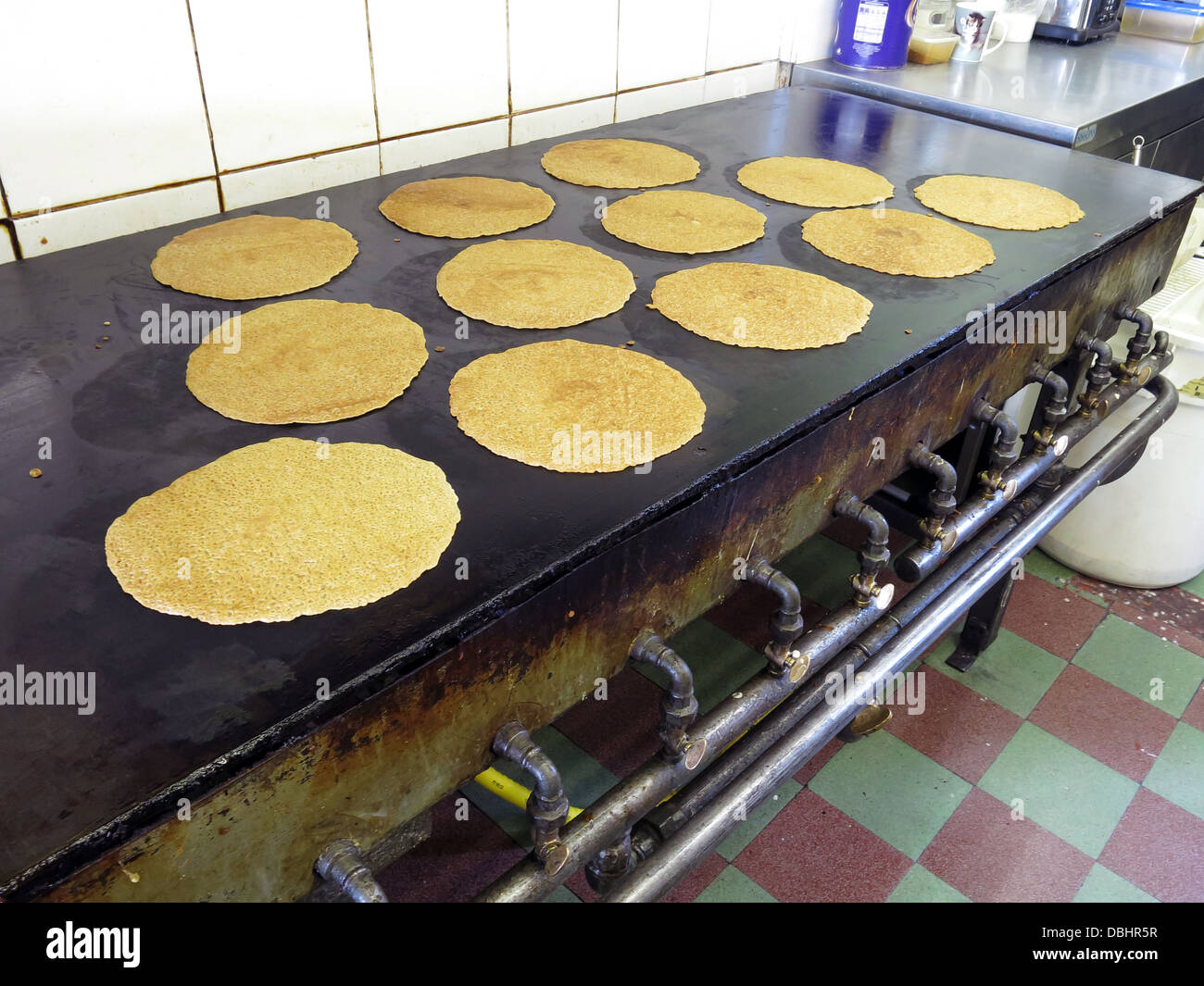 Interior of a traditional Stoke / Staffordshire Oatcake shop, with bright yellow frontage, cooking on an iron griddle - Stock Image