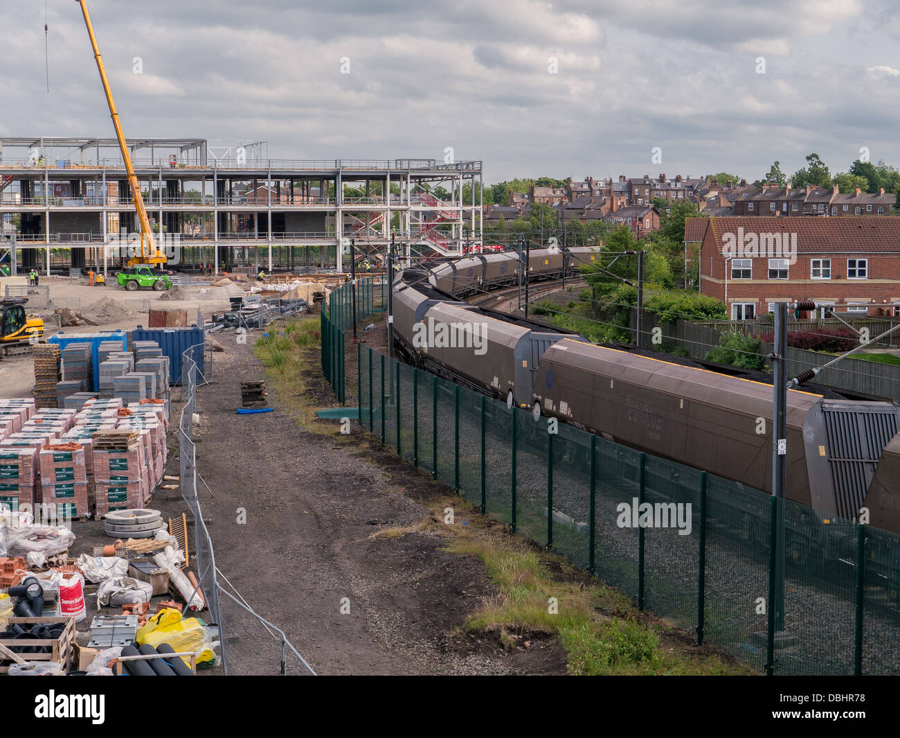 A freight train carrying coal moves slowly between a commercial building site and a residential area in York, UK. - Stock Image