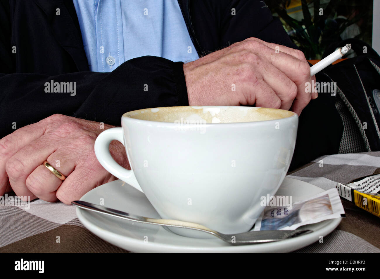 Man holding Cigarette with  Coffee cup in foreground - Stock Image