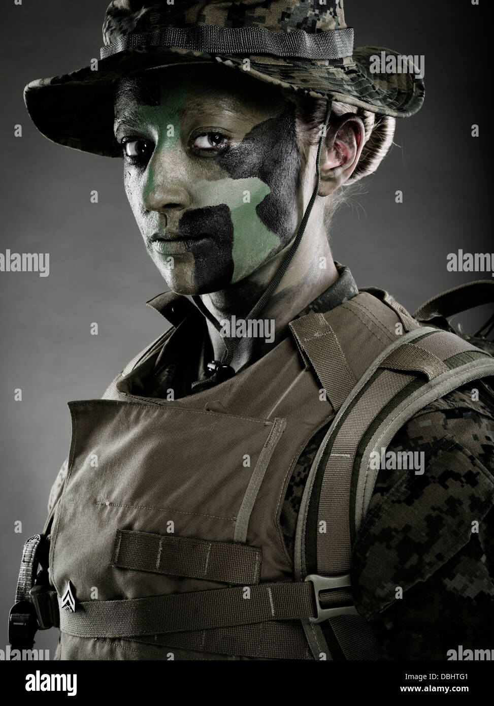 Portrait of Female United States Marine Corps Soldier in utility uniform MARPAT pixelated camouflage with camo face - Stock Image