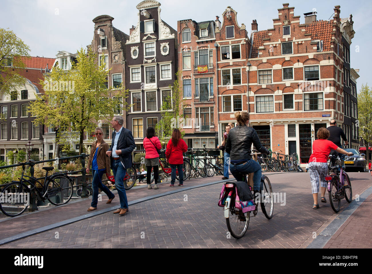 People on a bridge and houses on Prinsengracht, city of Amsterdam, Netherlands. - Stock Image