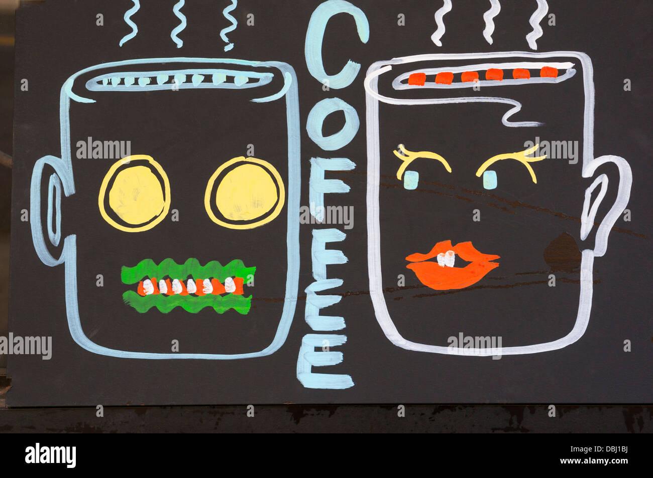 Coffee mugs cartoon in restaurant window - Stock Image