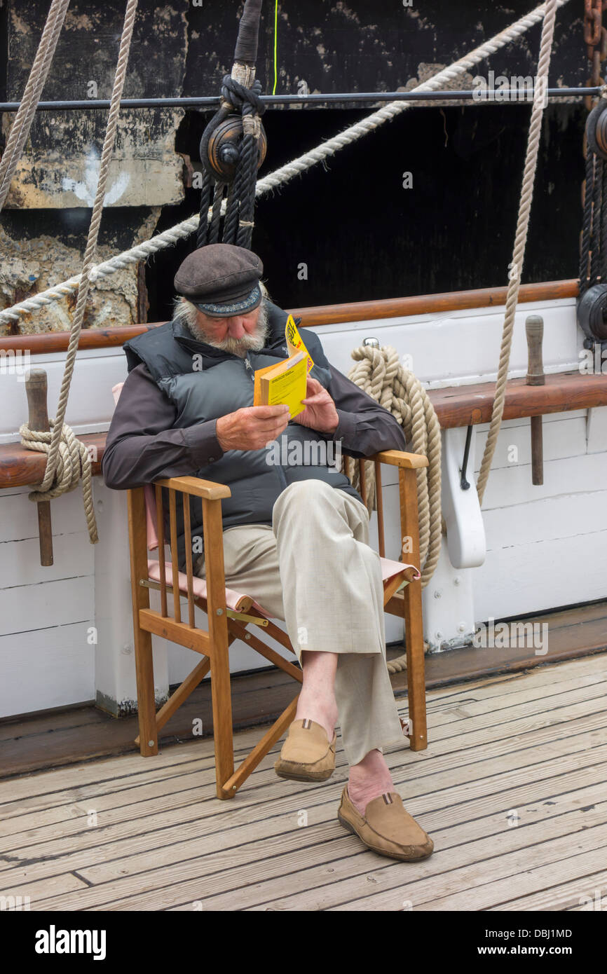 An Old Man Sitting On A Deck Chair Reading A Book On Board