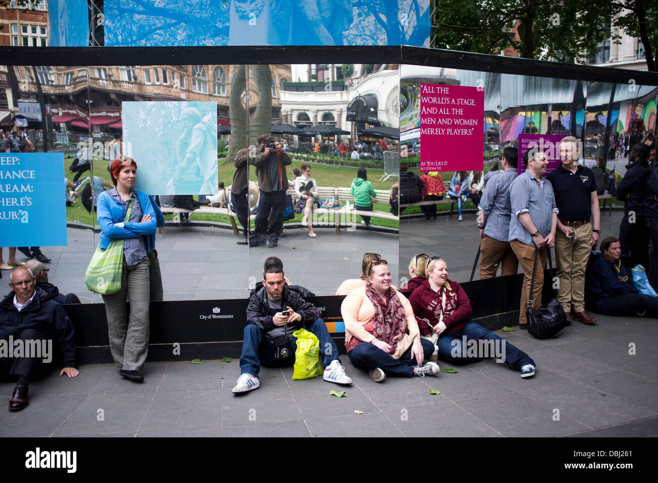 People on sidewalk Leicester Square - Stock Image