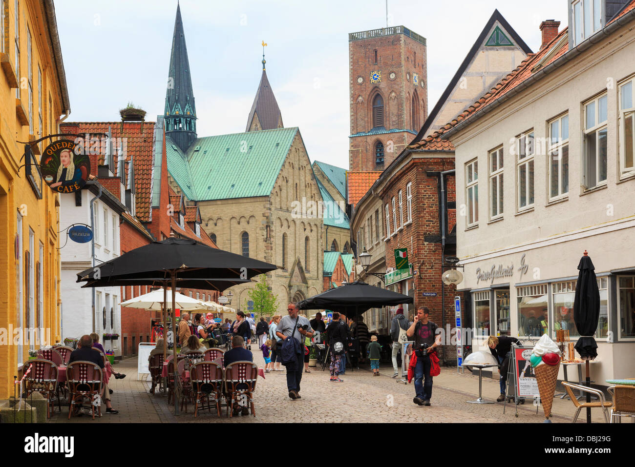 Outdoor cafes in pedestrianised cobbled main street in historic town with Our Lady Maria Cathedral beyond. Ribe - Stock Image