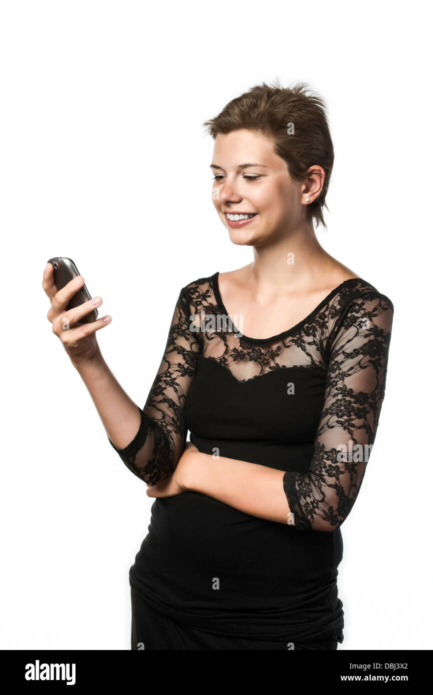 Young girl in black dress writing a short message (SMS) on their mobile phone, isolated on white background - Stock Image