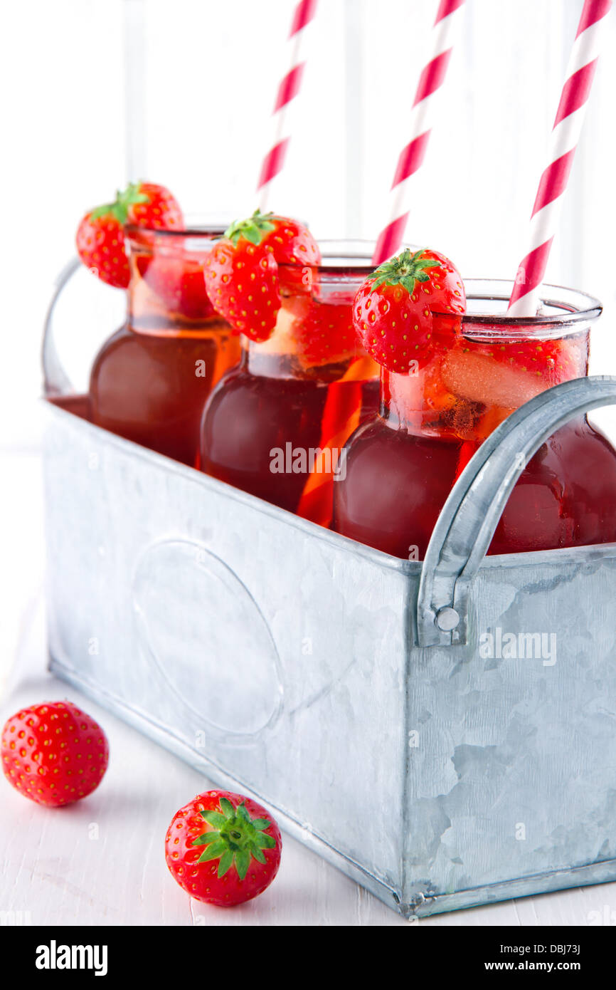 Glasses of red strawberry juice with frozen icecubes and striped straws in a metal vintage container Stock Photo