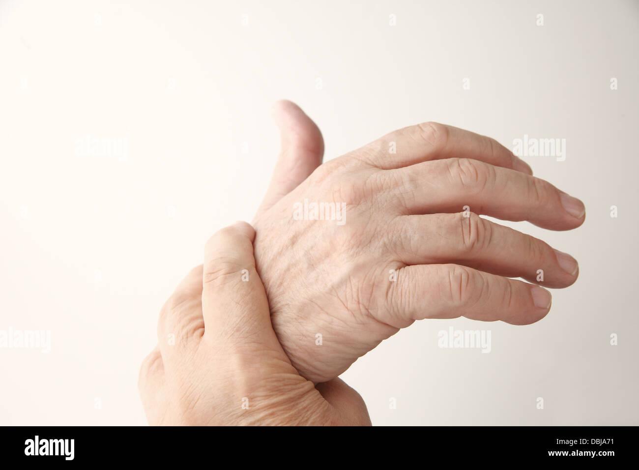 senior man holds his aching hand - Stock Image