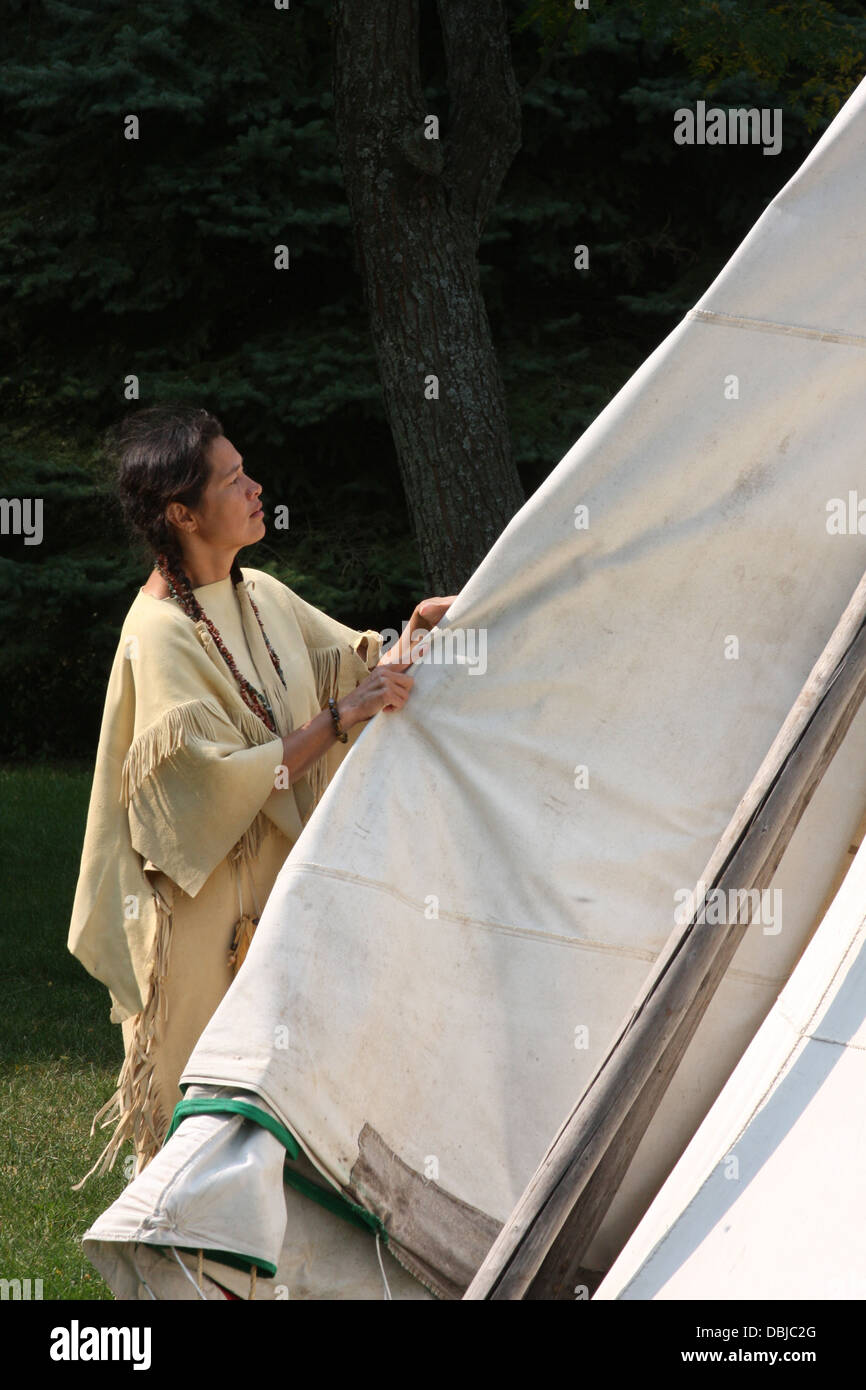 Native American Indian woman breaking down a tipi to move - Stock Image