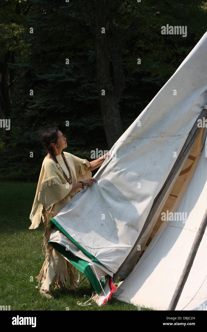 Native American Indian woman removing the sides to a tipi - Stock Image