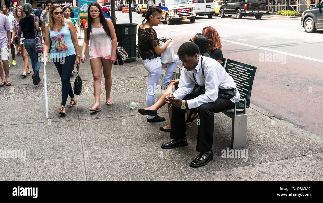 scantily clad young women pedestrians pass stylishly dressed young black man sitting on sidewalk bench East 34th - Stock Image