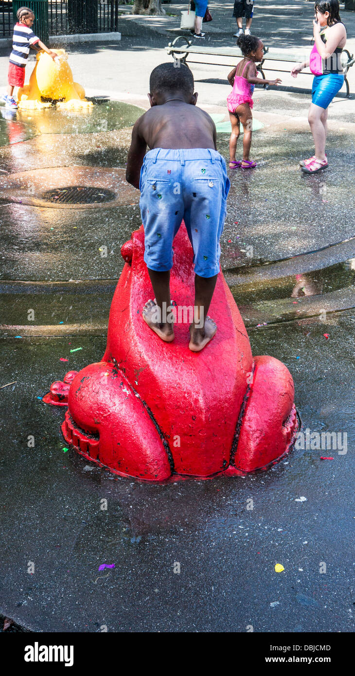 small black boy blue cutoffs & bare feet stands on bright red frog as other children play in water feature DeWitt - Stock Image