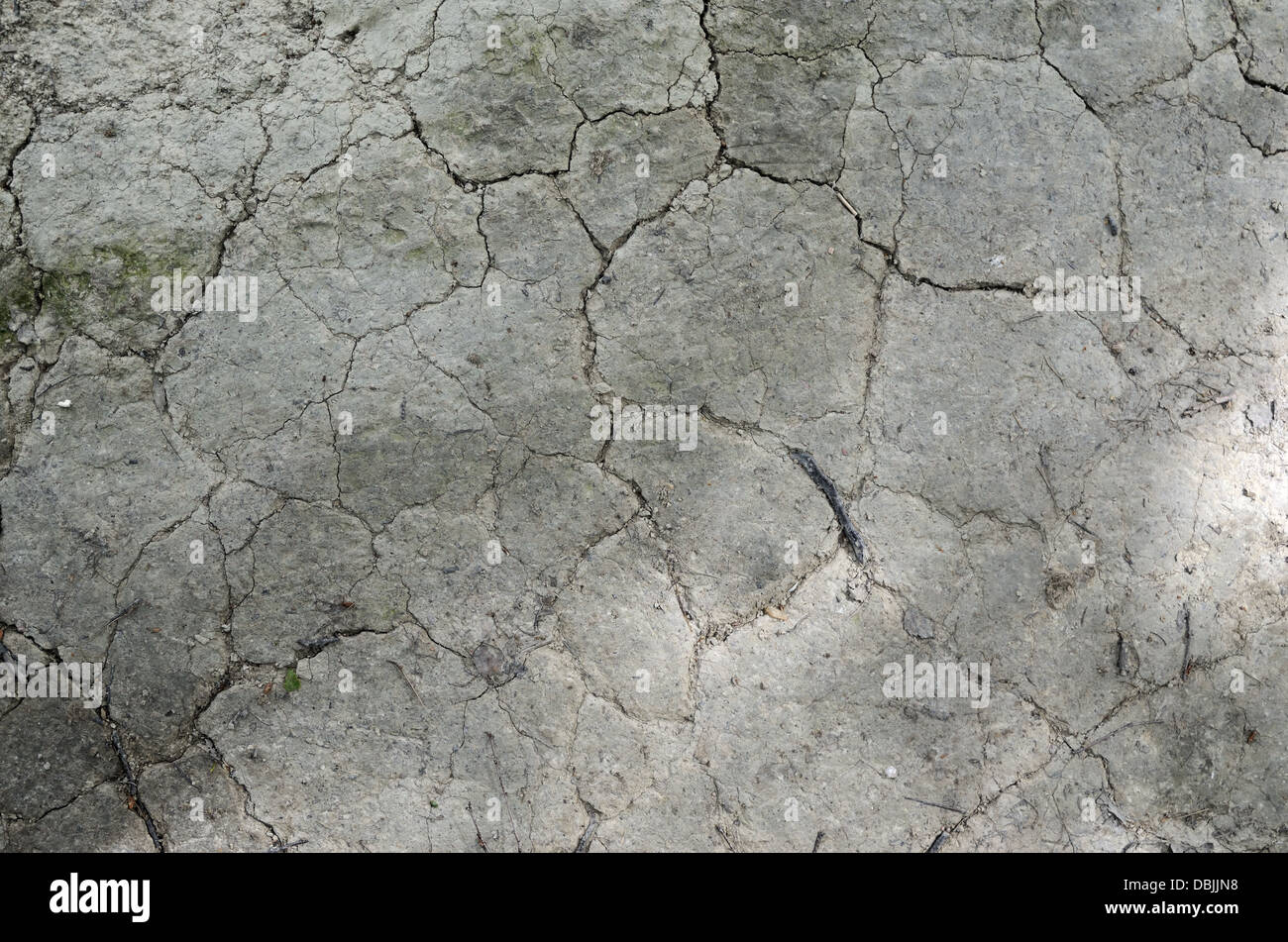 cracked clay gray surface with a spot of sunshine - Stock Image