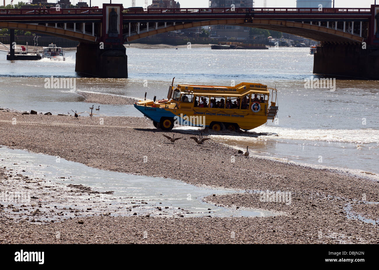 A WWII DUKW emerging from the Thames just below Vauxhall Bridge. Part of a London Duck tour. - Stock Image