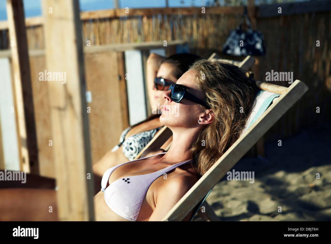 Young Women Sunbathing On Beach - Stock Image