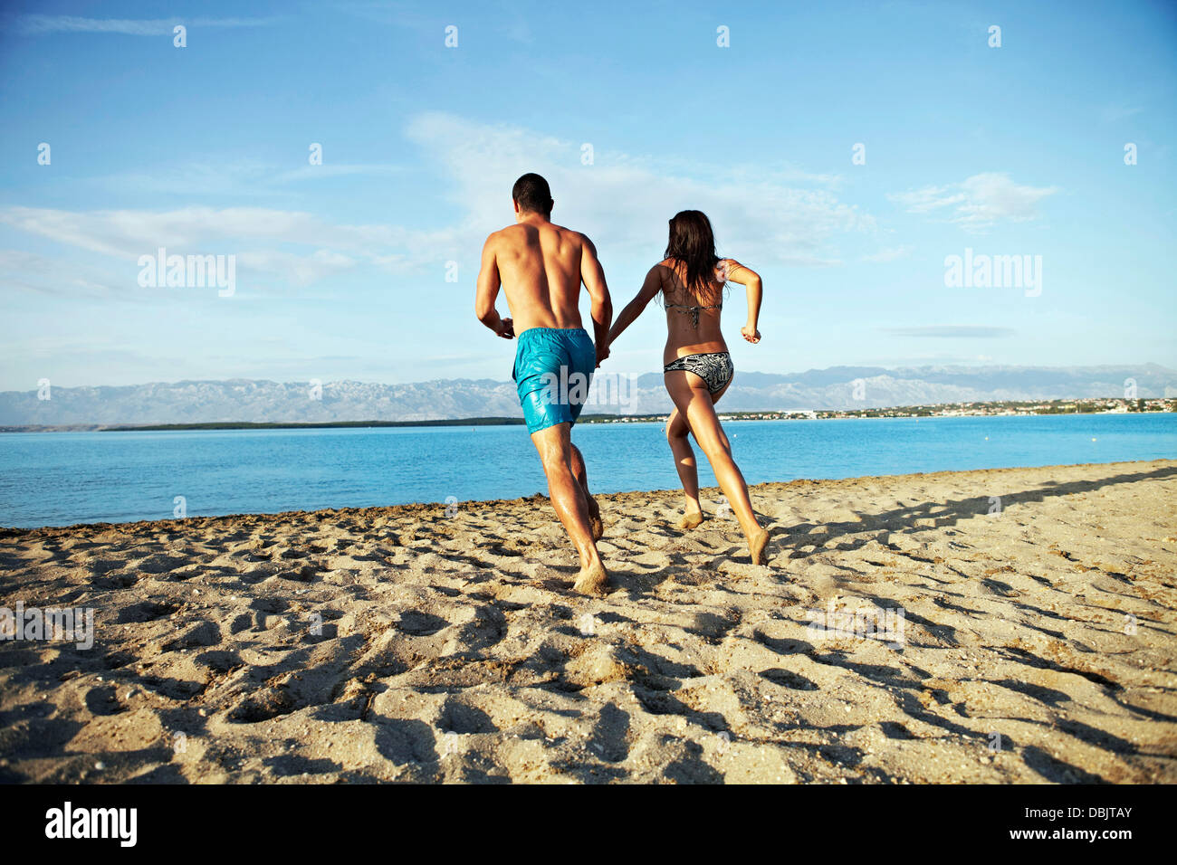 Young couple running into water - Stock Image