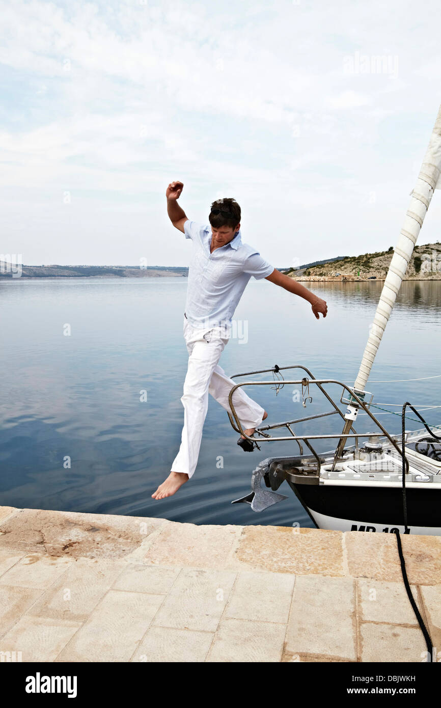 Croatia, Young man jumping onto pier - Stock Image