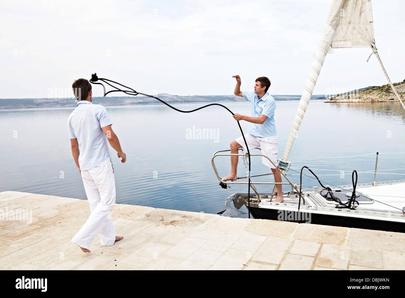 Croatia, Sailboat entering port, Two young men fixing rope Stock Photo