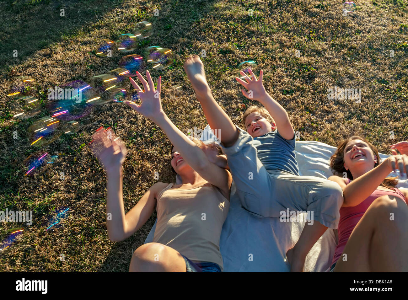 Persons In Garden Playing With Soap Bubbles, Croatia, Slavonia, Europe - Stock Image