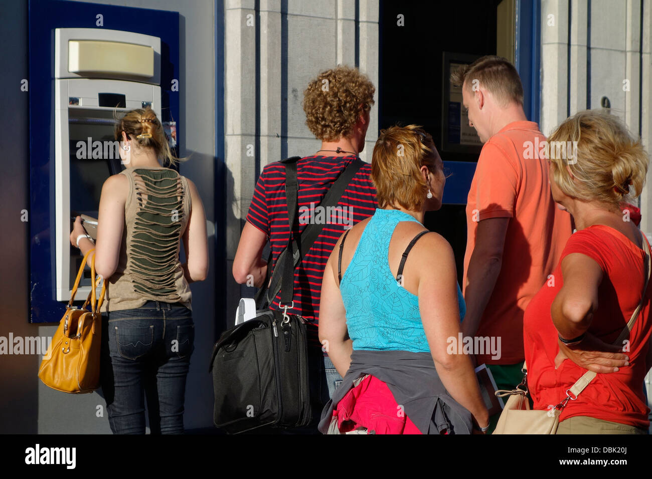Shoppers waiting in queue to collect money from ATM cash dispenser at cashpoint of bank in shopping street - Stock Image