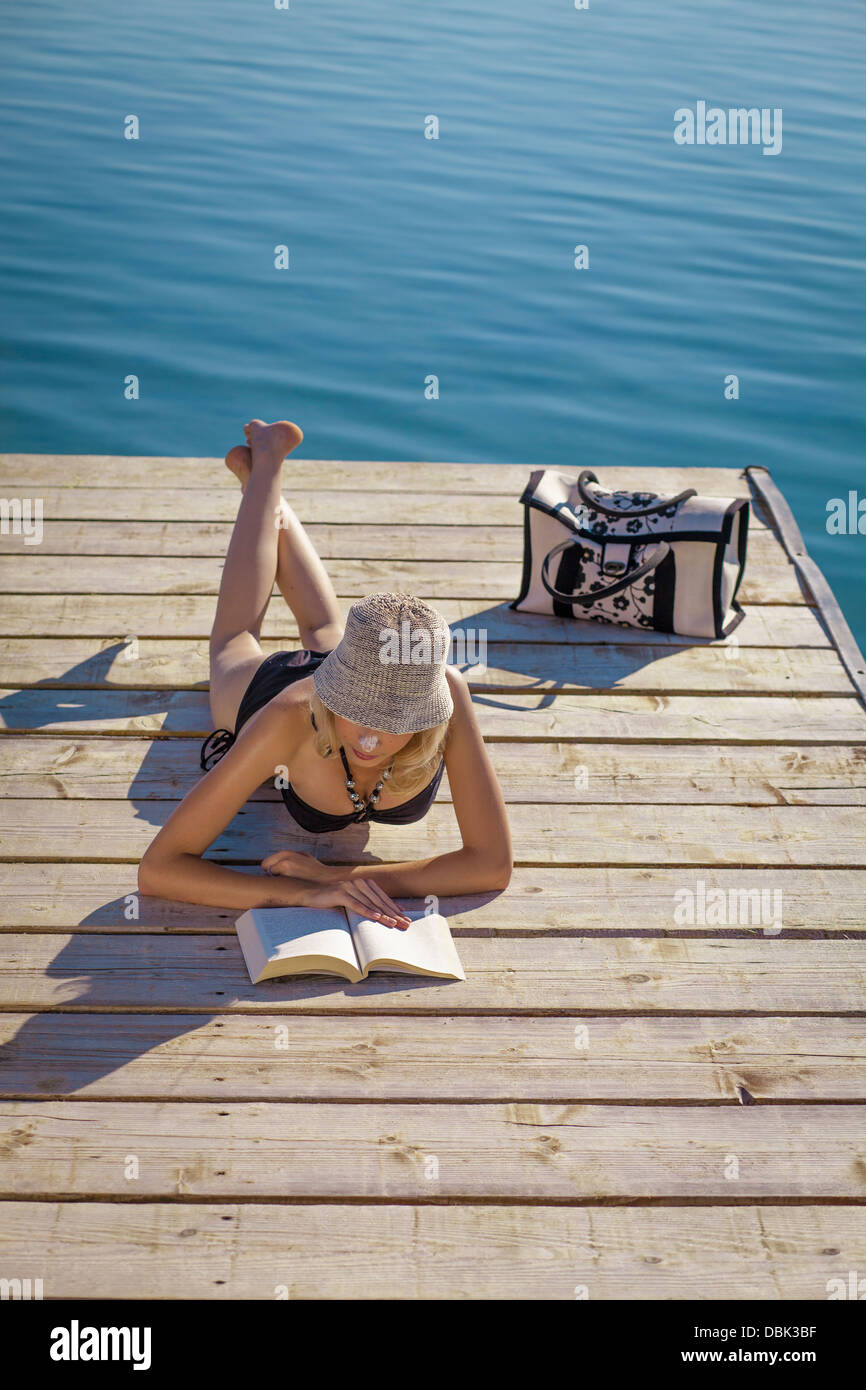 Croatia, Young woman with straw hat reads book on boardwalk, by the sea - Stock Image