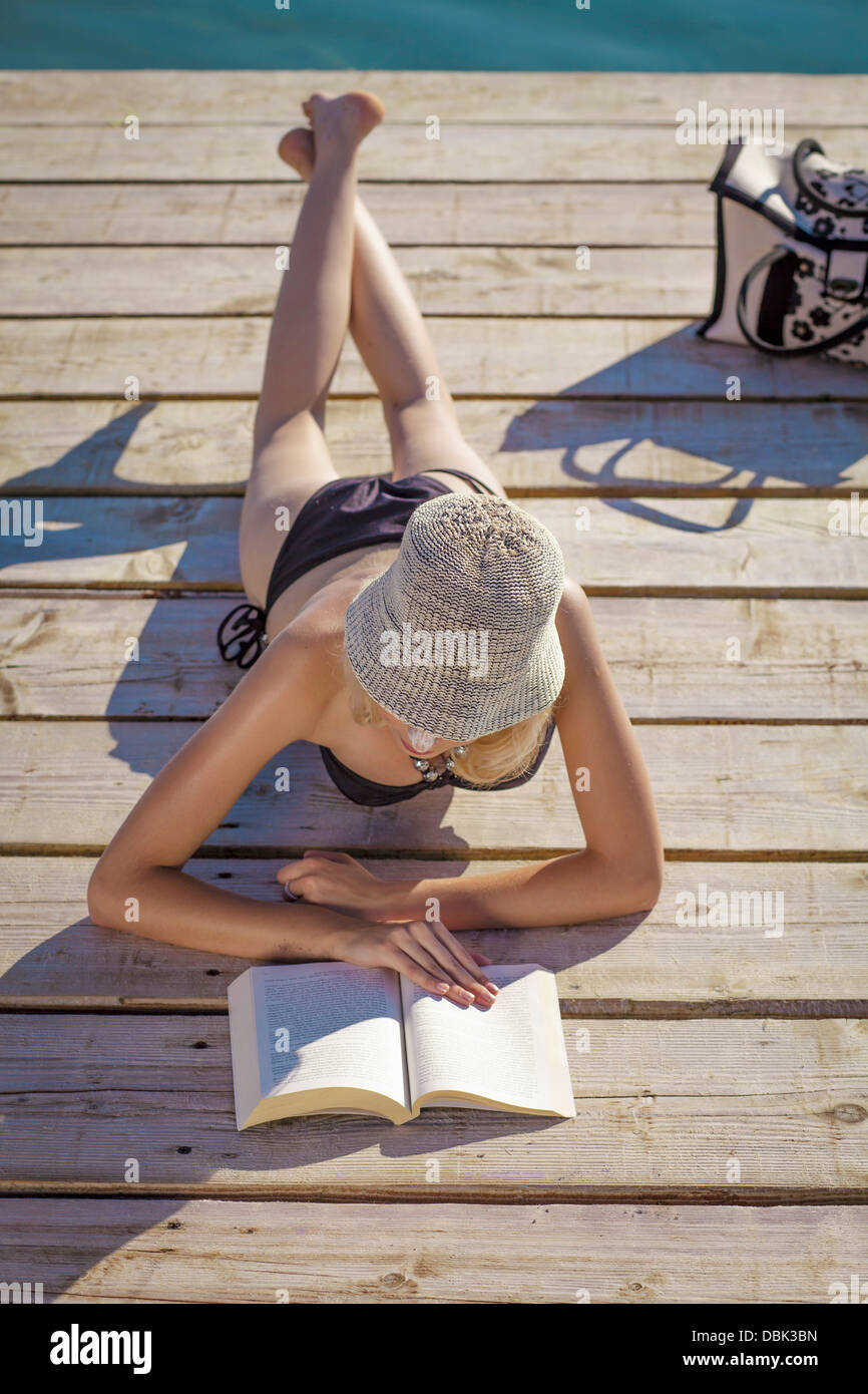 Croatia, Young woman with straw hat reads book on boardwalk - Stock Image