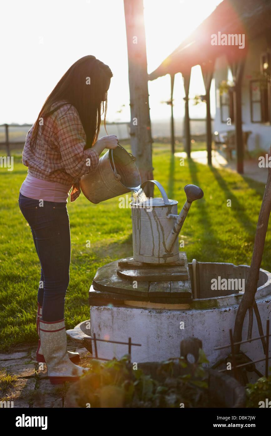 Young Woman On Farm Pouring Water in Bucket, Baranja, Croatia, Europe Stock Photo
