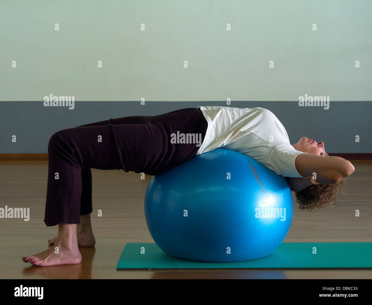 Woman doing Pilates exercise with ball - Stock Image
