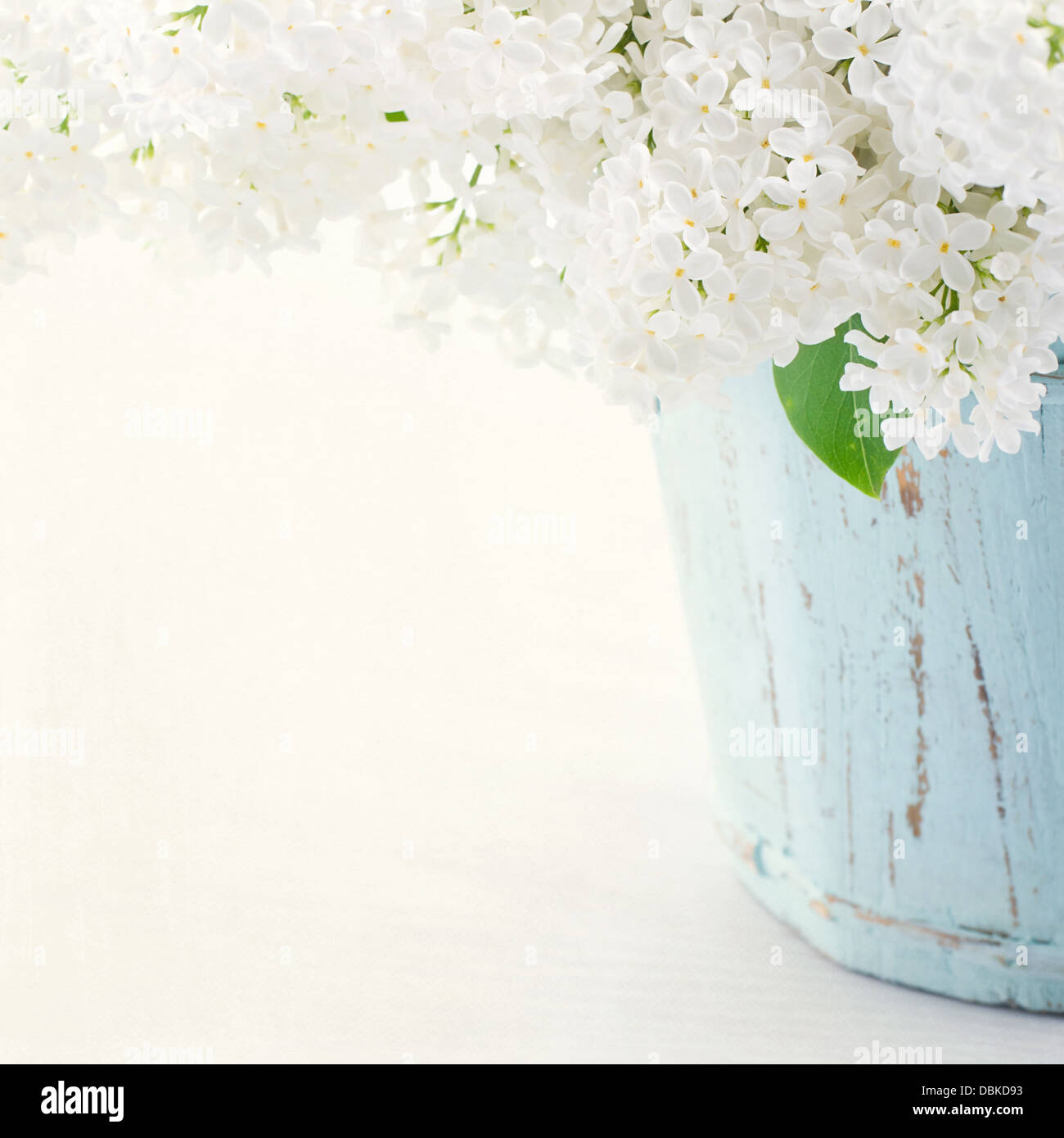 Bouquet of white lilac spring flowers in a wooden blue vase on light shabby chic background - Stock Image