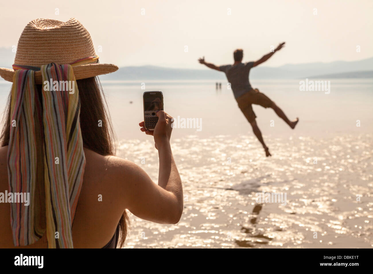 Croatia, Young woman on beach taking pictures - Stock Image