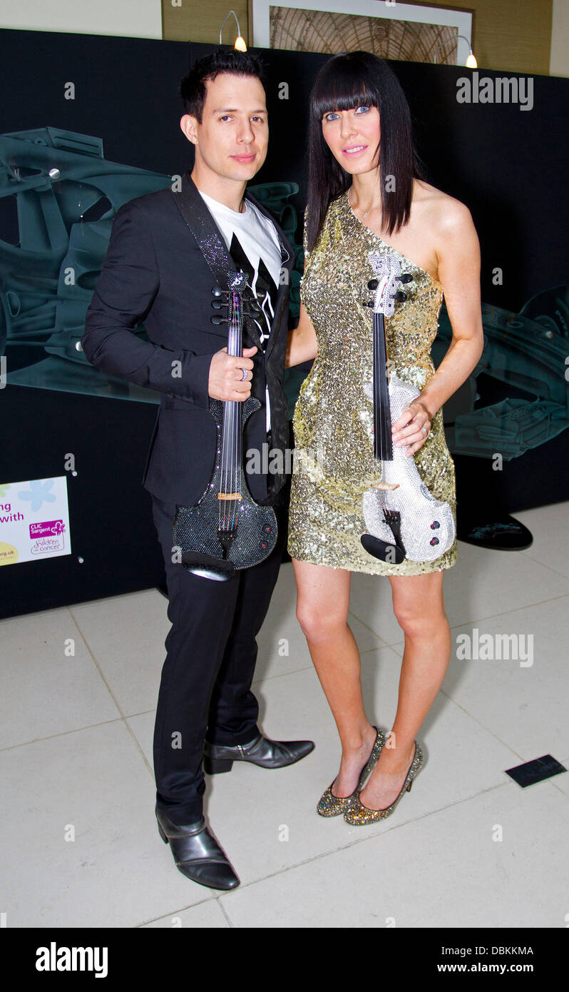 Lindsay Stoppard and guest pose with their diamond encrusted violins The Grand Prix Ball 2011 at The Hurlingham - Stock Image