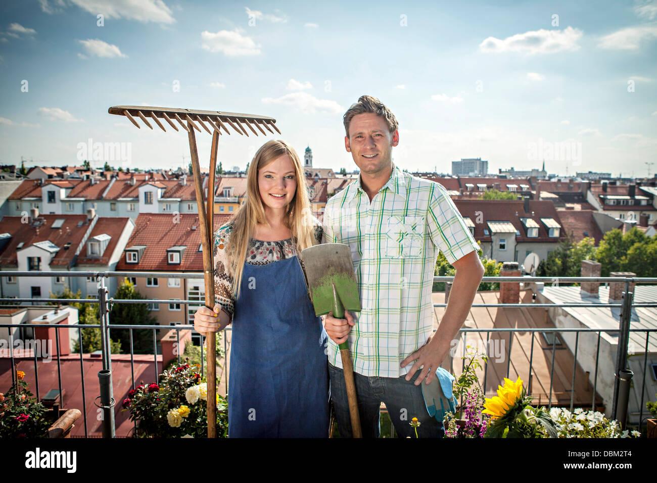 Couple On Balcony, Holding Garden Tools, Munich, Bavaria, Germany, Europe - Stock Image