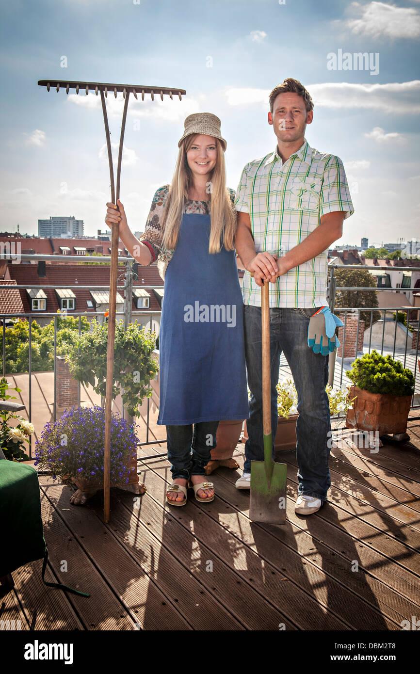 Couple On Balcony Holding Garden Rake And Shovel, Munich, Bavaria, Germany, Europe - Stock Image
