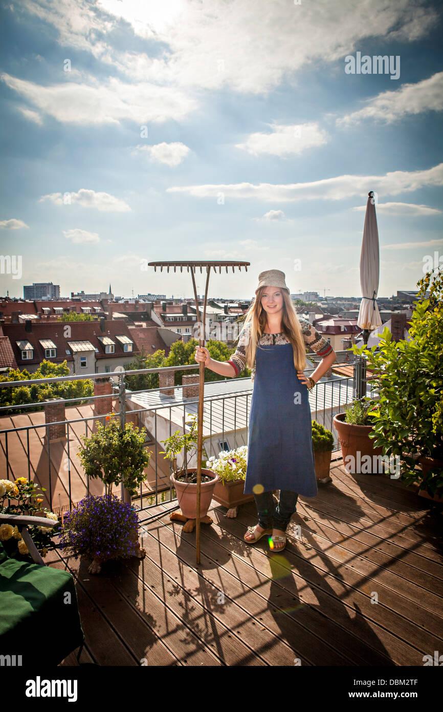 Young Woman On Balcony Holding Garden Rake, Munich, Bavaria, Germany, Europe - Stock Image