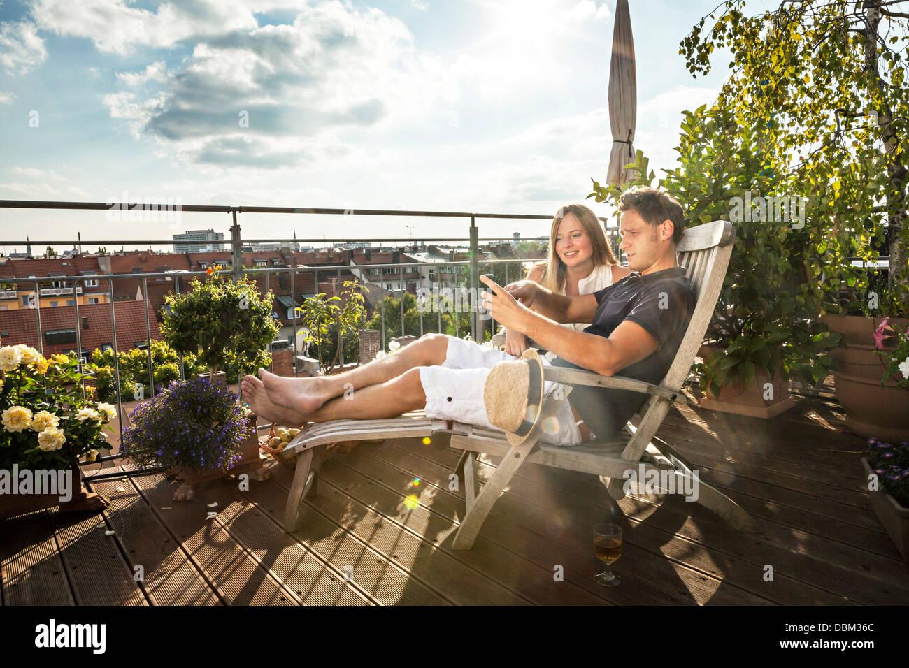 Couple On Balcony Using Mobile Phone, Munich, Bavaria, Germany, Europe - Stock Image