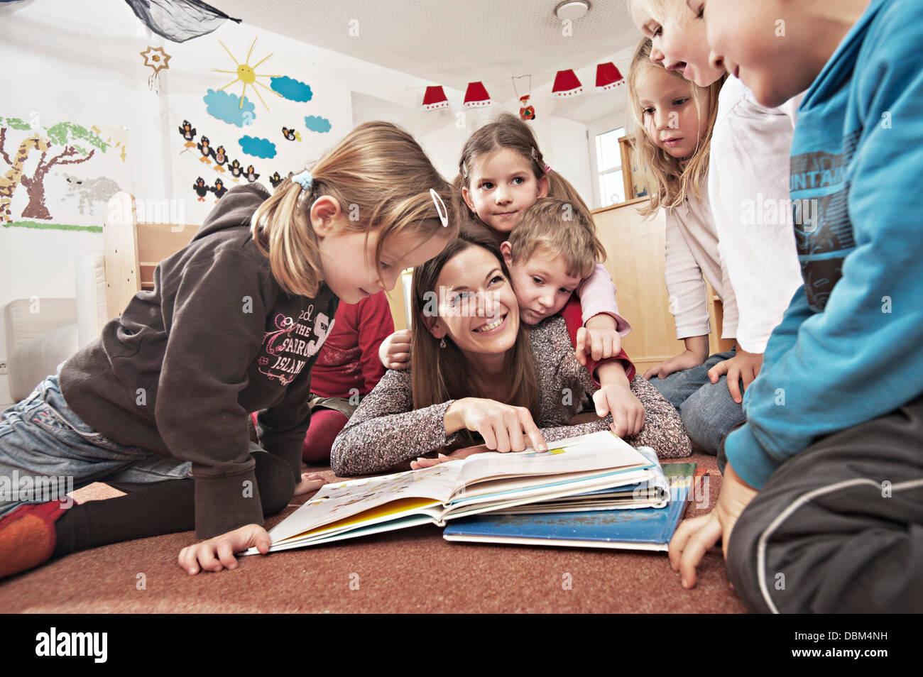 Female Carer And Children Reading A Book Together, Kottgeisering, Bavaria, Germany, Europe - Stock Image