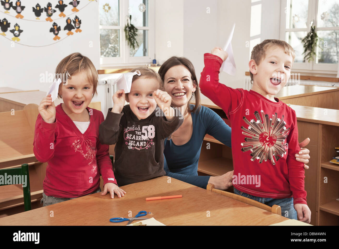 Children In Nursery School Holding Paper Planes, Kottgeisering, Bavaria, Germany, Europe - Stock Image