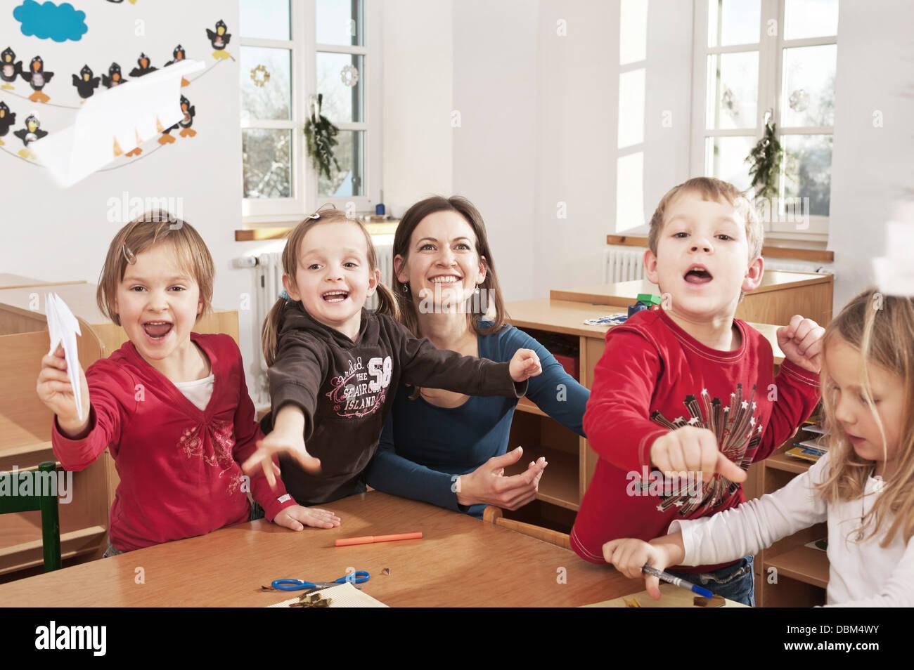 Children In Nursery School Throwing Paper Planes In The Air, Kottgeisering, Bavaria, Germany, Europe - Stock Image