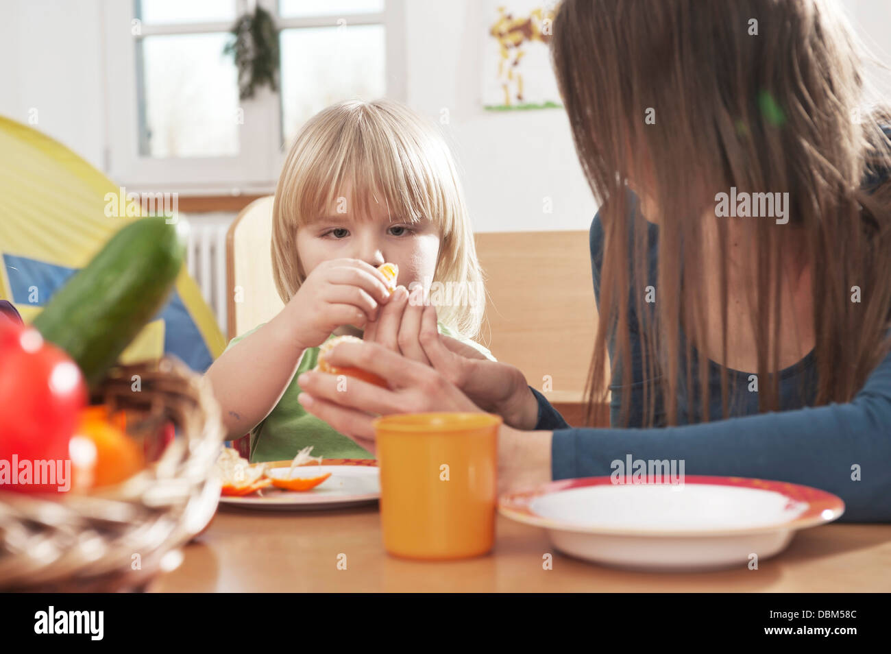 Female Carer And Boy Sitting At Table, Kottgeisering, Bavaria, Germany, Europe - Stock Image