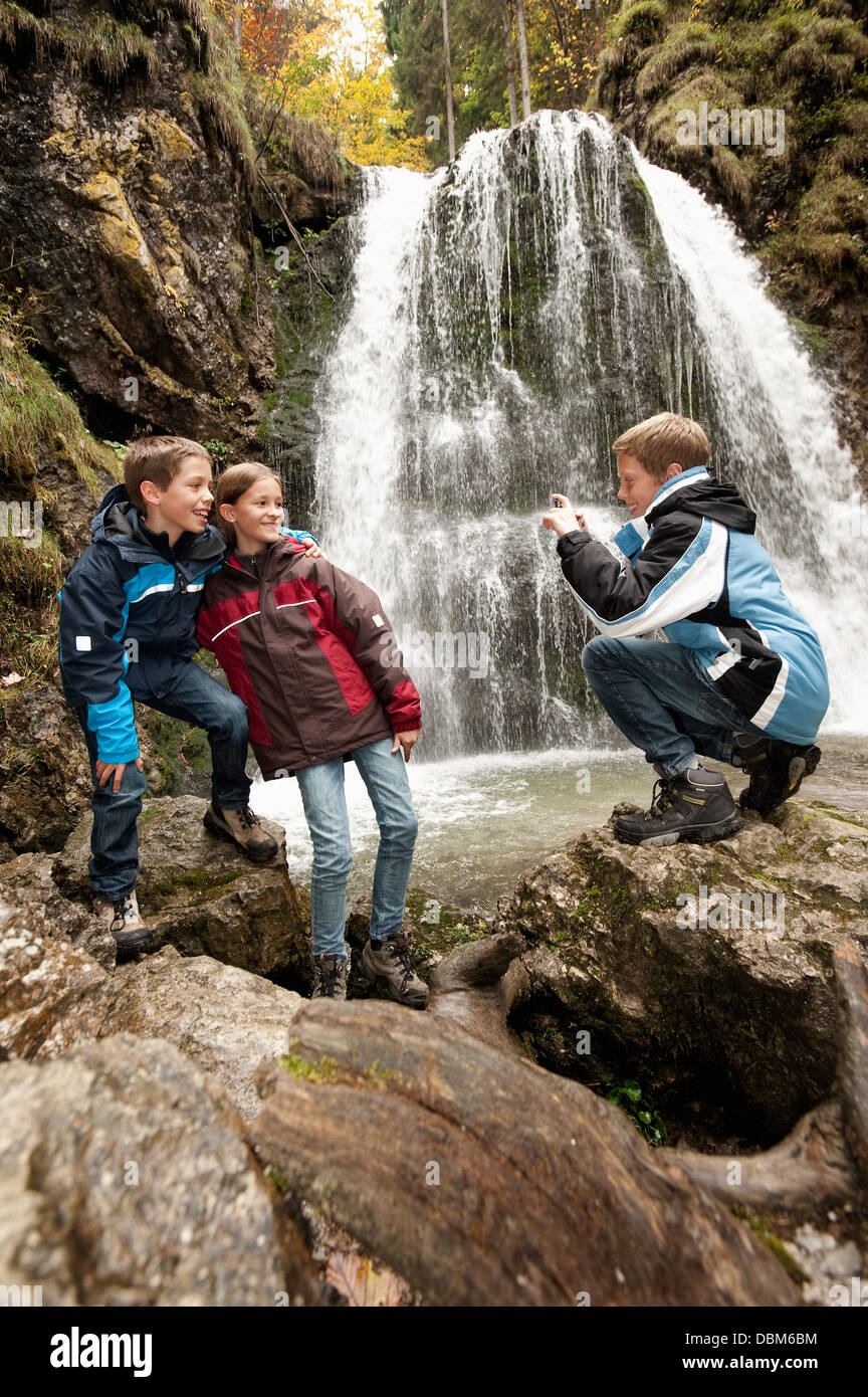 Three Children In Front Of A Waterfall, Bavaria, Germany, Europe - Stock Image